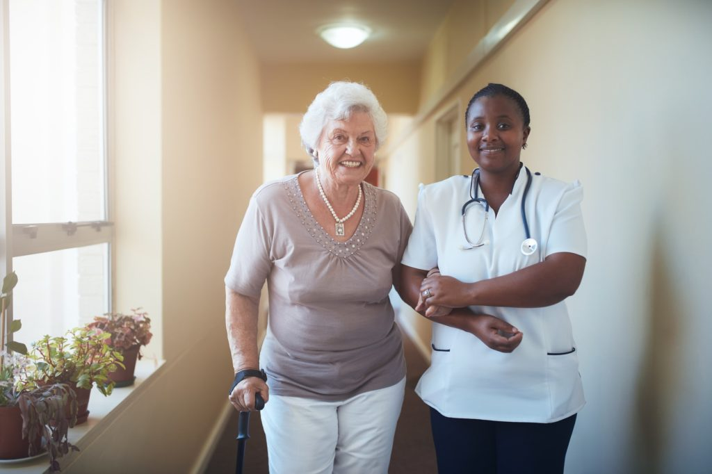 Nurse assisting a senior patient to walk